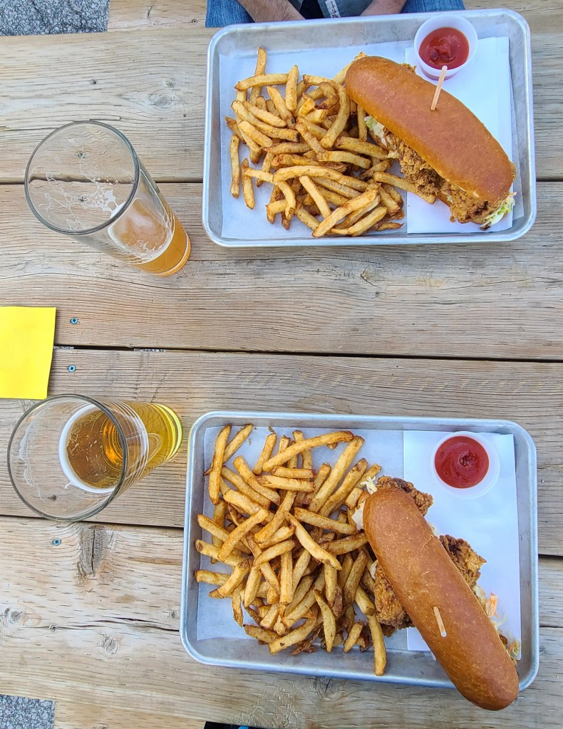 A birds eye view image of two meals on a picnic table including friend chicken sandwiches, french fries and beer.