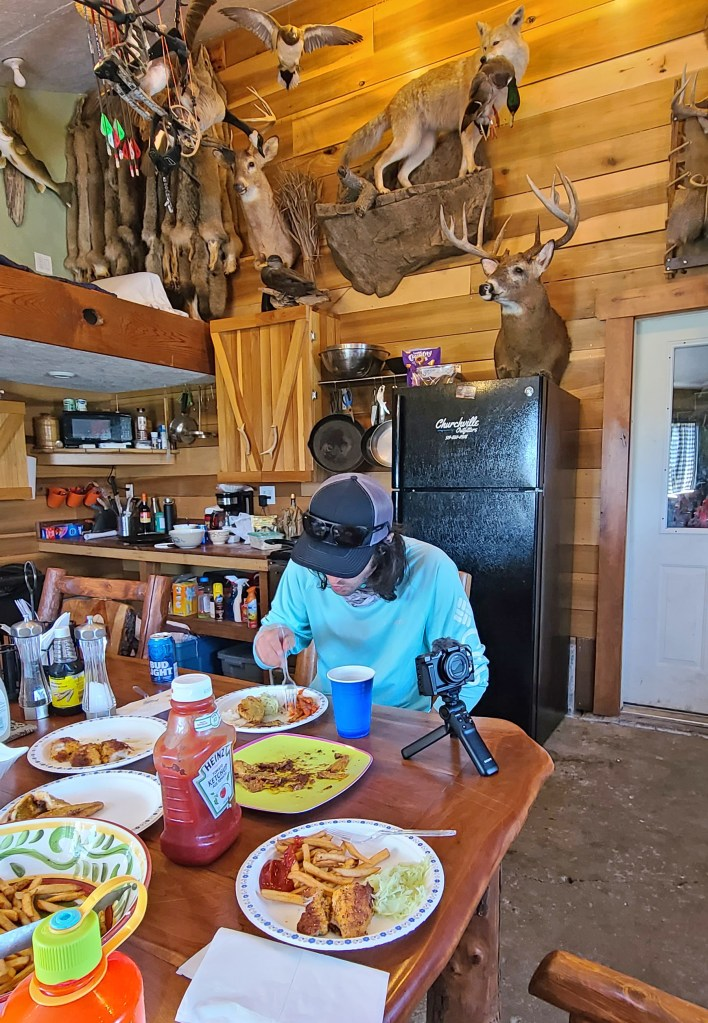 A man sitting at a dining room table eating pan fried walleye in a rustic dining room with trophy deer and other animals mounted the wall