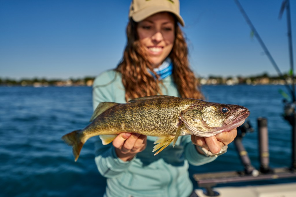 A female angler smiling and holding a walleye caught while fishing on the St. Clair River/Lake Huron