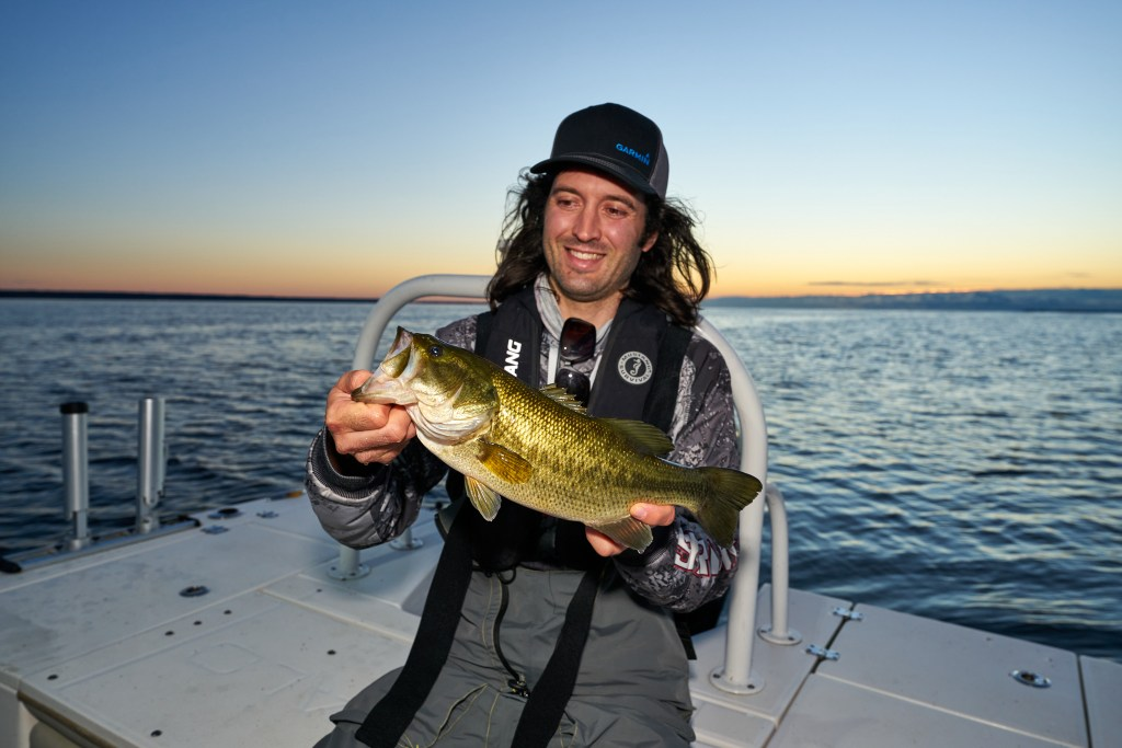 A man smiling and holding up a largemouth bass