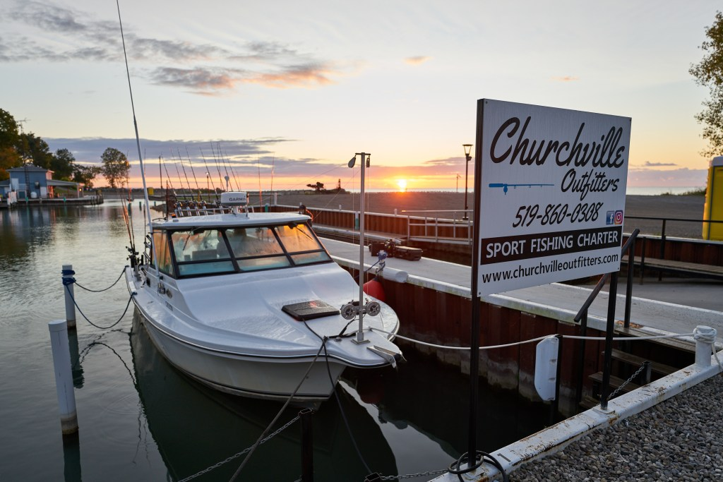 A charter boat tied up at the docks at Port Glasgow Yacht Club & Marina with the sunrise in the background over Lake Erie.