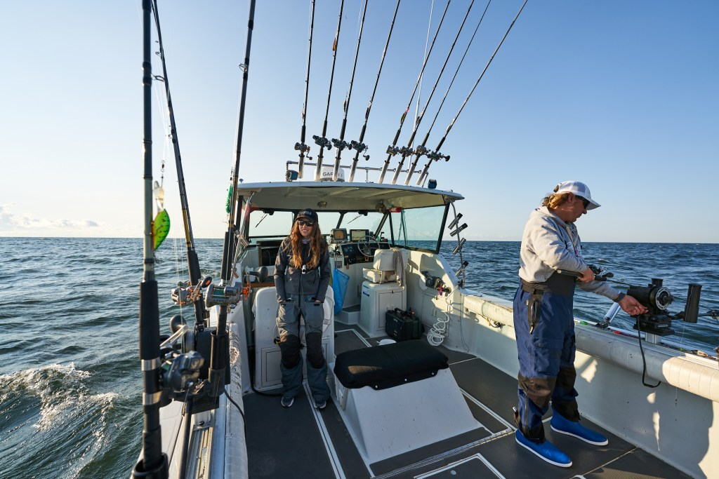 An image from the rear of a fishing boat with many fishing rods and a man and woman on board. The man is setting a line in the water.