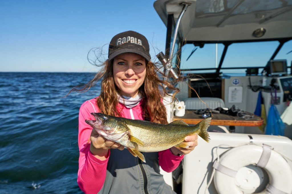 A woman aboard a boat smiling and holding a Lake Erie walleye