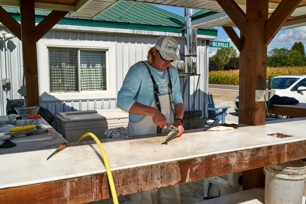 A man cleaning a walleye at a fish cleaning station