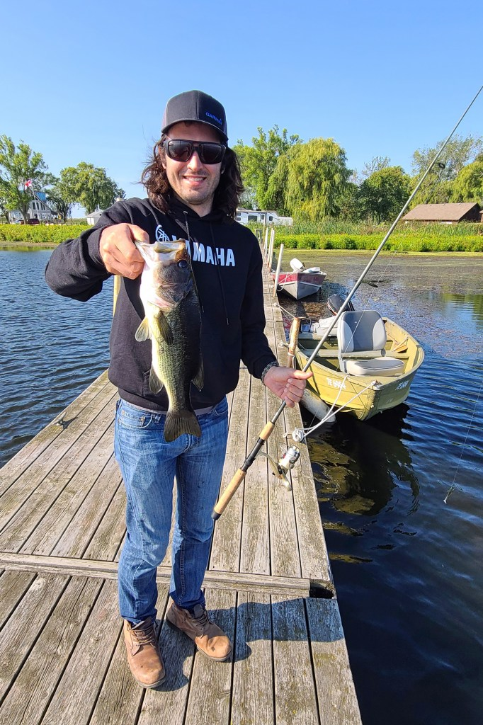 A man standing on a dock smiling with a fishing rod in one hand and a largemouth bass in the other