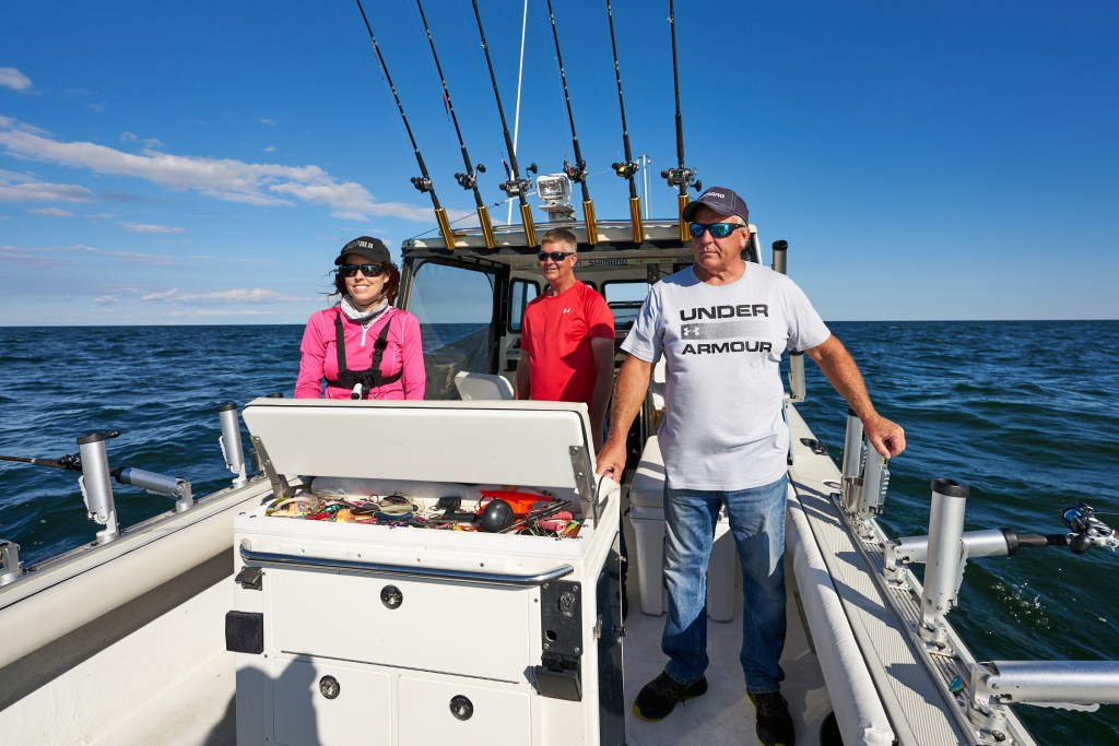 Three anglers standing aboard a boat smiling and looking back at the fishing rods waiting for a bite